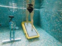 Giovane donna che pareggia su una pedana mobile subacquea fotografia stock
