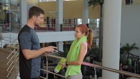 Giovane donna che parla con l'istruttore che sta in società polisportiva archivi video