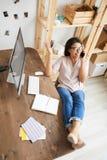 Giovane donna che parla dal telefono allo scrittorio fotografie stock