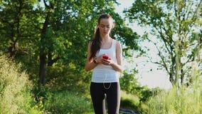 Giovane donna che parla dal telefono facendo uso delle cuffie all'aperto archivi video