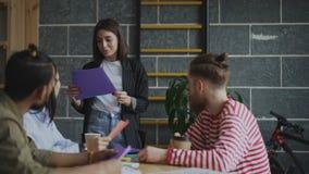 Giovane donna che parla e che discute le nuove idee con il gruppo creativo durante il 'brainstorming' dei progetti start-up in cr archivi video