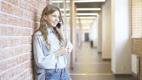 Giovane donna che parla sul corridoio in costruzione del telefono Fotografie Stock Libere da Diritti