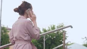 Giovane donna che parla sul suo telefono cellulare sulla via stock footage
