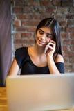 Giovane donna che parla sul telefono cellulare e che utilizza computer portatile nel caffè Fotografia Stock