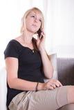 Giovane donna che parla sul telefono che si siede nella sedia del bracciolo Fotografie Stock