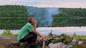 Giovane donna che parla sul telefono da un fuoco di accampamento archivi video