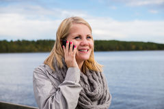 Giovane donna che parla sul telefono e sul sorridere Immagini Stock