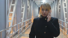 Giovane donna che parla sul telefono e sulla passeggiata nella notte dell'interno Ritratto della ragazza attraente che parla sul  archivi video