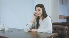 Giovane donna che parla sul telefono ed il caffè o il tè bevente immagine stock libera da diritti