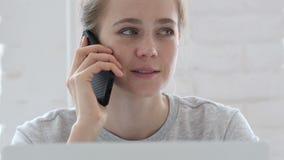 Giovane donna che parla sul telefono mentre lavorando al computer portatile video d archivio