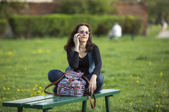 Giovane donna che parla sul telefono mentre sedendosi Immagini Stock