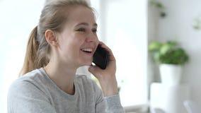 Giovane donna che parla sul telefono nel posto di lavoro del sottotetto archivi video