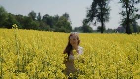 Giovane donna che passa i fiori commoventi HD del campo giallo video d archivio
