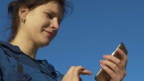 Giovane donna che passa in rassegna Internet sul telefono e che chiacchiera all'aperto Movimento lento, 120 fps stock footage