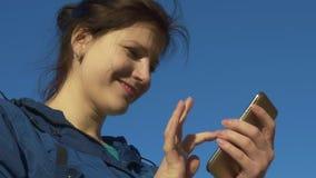 Giovane donna che passa in rassegna Internet sul telefono e che chiacchiera all'aperto Movimento lento, 120 fps archivi video