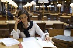 Giovane donna che pensa nella libreria Fotografia Stock Libera da Diritti
