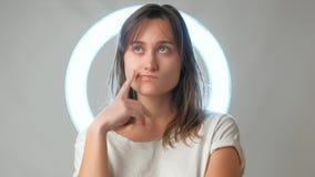 Giovane donna che pensa a qualcosa e che gioca con i capelli stock footage