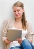 Giovane donna che per mezzo del calcolatore del ridurre in pani Immagini Stock
