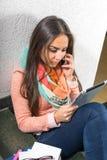 Giovane donna che per mezzo del cellulare Fotografia Stock