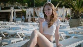 Giovane donna che per mezzo del cellulare mentre trovandosi sul lettino sulla spiaggia video d archivio