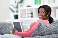 Giovane donna che per mezzo del computer della compressa Immagine Stock