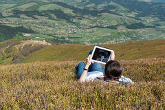 Giovane donna che per mezzo del computer della compressa all'aperto Fotografia Stock