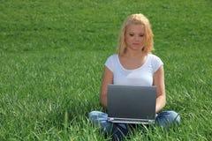 Giovane donna che per mezzo del computer portatile all'esterno Immagini Stock Libere da Diritti