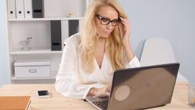 Giovane donna che per mezzo del computer portatile all'ufficio moderno stock footage