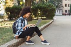 Giovane donna che per mezzo del computer portatile all'università Immagine Stock