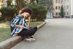 Giovane donna che per mezzo del computer portatile all'università Fotografia Stock