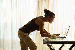 Giovane donna che per mezzo del computer portatile che si appoggia contro la tabella Fotografia Stock Libera da Diritti