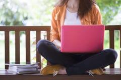 Giovane donna che per mezzo del computer portatile del computer sul banco immagine stock