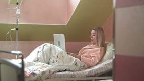 Giovane donna che per mezzo del computer portatile che ha video chiacchierata sul letto di ospedale video d archivio