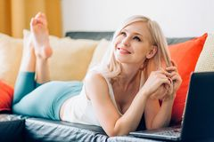 Giovane donna che per mezzo del computer portatile mentre rilassandosi sul sofà immagini stock libere da diritti