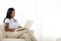 Giovane donna che per mezzo del computer portatile nel paese Fotografie Stock Libere da Diritti