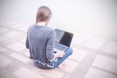Giovane donna che per mezzo del computer portatile sui punti all'aperto Immagine Stock
