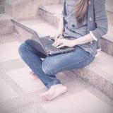Giovane donna che per mezzo del computer portatile sui punti all'aperto Fotografia Stock