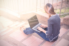 Giovane donna che per mezzo del computer portatile sui punti all'aperto Fotografie Stock