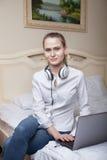 Giovane donna che per mezzo del computer portatile sul letto Immagine Stock Libera da Diritti