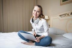 Giovane donna che per mezzo del computer portatile sul letto Fotografia Stock Libera da Diritti