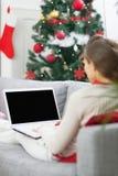 Giovane donna che per mezzo del computer portatile vicino all'albero di Natale. retrovisione Fotografie Stock Libere da Diritti
