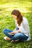 Giovane donna che per mezzo del suo calcolatore del ridurre in pani Fotografie Stock Libere da Diritti