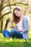 Giovane donna che per mezzo del suo calcolatore del ridurre in pani Fotografia Stock