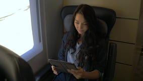 Giovane donna che per mezzo del suo computer della compressa mentre viaggiando in treno Concetto di applicazione di viaggio video d archivio