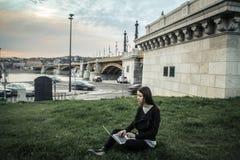 Giovane donna che per mezzo del suo computer portatile Fotografia Stock Libera da Diritti
