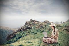Giovane donna che per mezzo del suo computer portatile Immagini Stock Libere da Diritti