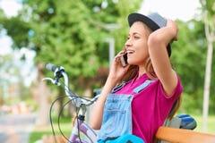 Giovane donna che per mezzo del suo Smart Phone al parco Fotografie Stock