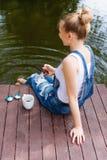 Giovane donna che per mezzo del suo smartphone che si siede sul pilastro e bevendo caffè caldo Immagini Stock Libere da Diritti