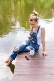 Giovane donna che per mezzo del suo smartphone che si siede sul pilastro e bevendo caffè caldo Immagine Stock