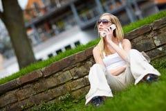 Giovane donna che per mezzo del suo telefono Fotografia Stock